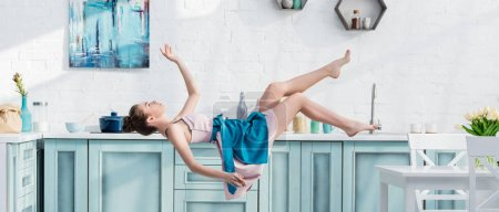 Photo pour Plan panoramique de jeune femme en tablier et robe lévitant dans l'air dans la cuisine - image libre de droit