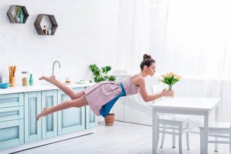 Photo pour Jeune femme pieds nus élégante en lévitation dans l'air avec tulipes - image libre de droit