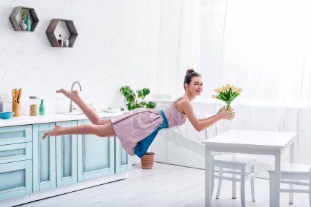 Photo for Young happy elegant barefoot woman levitating in air with bouquet of tulips - Royalty Free Image