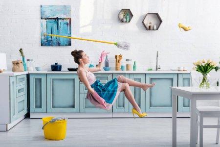 Photo pour Élégante fille dans tablier lévitation avec serpillière et chaussures à talons jaunes pendant le nettoyage de la maison dans la cuisine - image libre de droit