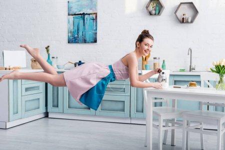 glücklich schöne junge Frau schwebt in der Luft und gießt Tee in Tasse aus Teekanne in der Küche