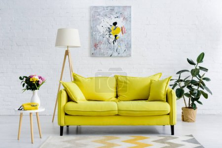 Photo for Interior of cozy living room with bright yellow elements, decor and retro telephone - Royalty Free Image