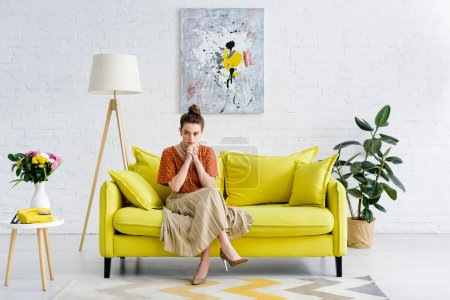 Photo for Pensive elegant young woman sitting with crossed legs and clenched hands on yellow sofa in living room - Royalty Free Image