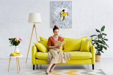 Photo for Elegant woman sitting in living room and reading book - Royalty Free Image