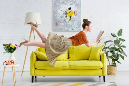 Photo for Elegant young woman levitating in air while reading book - Royalty Free Image