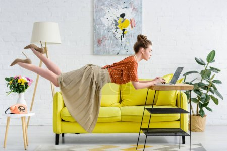 Photo for Elegant young woman levitating in air and using laptop in living room - Royalty Free Image