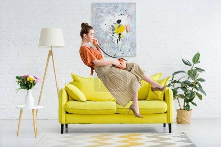 Foto de Vista lateral del elegante joven levitando en el aire y hablando por teléfono vintage en la sala de estar - Imagen libre de derechos