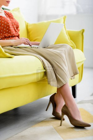 Photo for Cropped view of young woman in heeled shoes sitting on yellow sofa and using laptop - Royalty Free Image