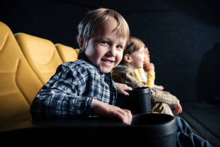 Photo for Cute boy looking at camera while sitting with friends in cinema - Royalty Free Image