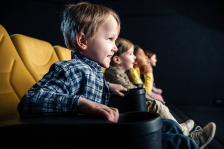 Photo for Smiling multicultural friends sitting in cinema and watching movie together - Royalty Free Image