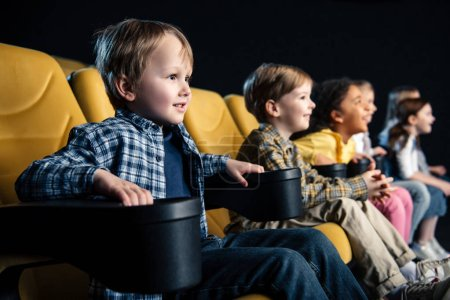 Photo for Selective focus of smiling multicultural friends sitting in cinema and watching movie - Royalty Free Image