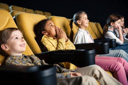 Photo pour Amis multiculturelles souriants assis au cinéma et regarder le film ensemble - image libre de droit