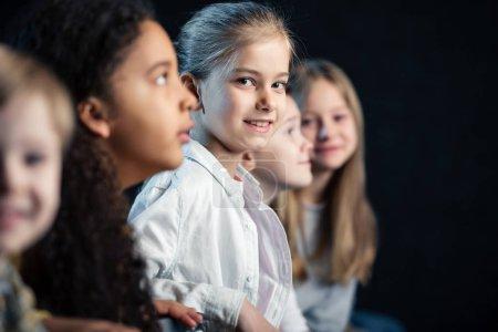 Photo pour Mise au point sélective d'adorables enfants assis au cinéma et regarder film - image libre de droit