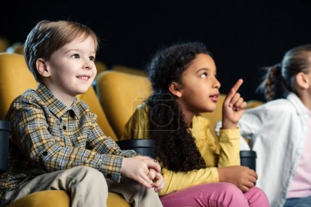Photo pour Mignonne enfant africain-américaine pointant avec le doigt tout en regardant le film avec des amis au cinéma - image libre de droit