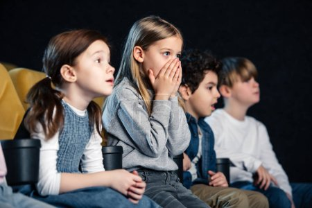 Photo for Cute child holding hands on face while watching movie with multicultural friends - Royalty Free Image
