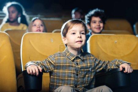 Photo pour Concentré de garçon en regardant le film au cinéma avec des amis multiculturelles - image libre de droit