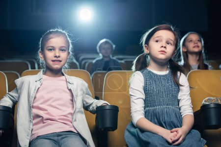Photo for Cute children sitting in cinema together with friends and watching movie - Royalty Free Image