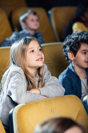 Photo for Selective focus of smiling multicultural friends watching movie in cinema together - Royalty Free Image
