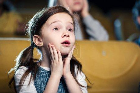 Photo pour Mise au point sélective de mignon enfant inquiet, je regarde le film au cinéma - image libre de droit
