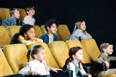 Photo for Smiling multicultural friends watching movie in cinema together - Royalty Free Image