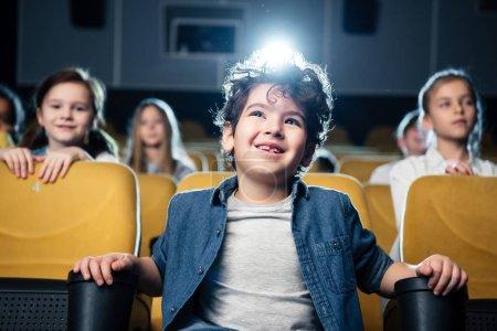 Foto de Sonrisa de película ver de raza mixta boy en el cine junto a amigos multiculturales - Imagen libre de derechos
