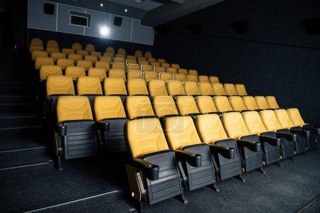 Foto de Sala de cine oscura con confortables asientos vacíos con sostenedores de taza - Imagen libre de derechos