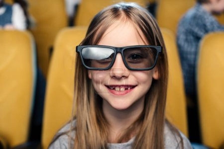 Photo for Selective focus of smiling child in 3d glasses looking at camera while sitting in cinema - Royalty Free Image