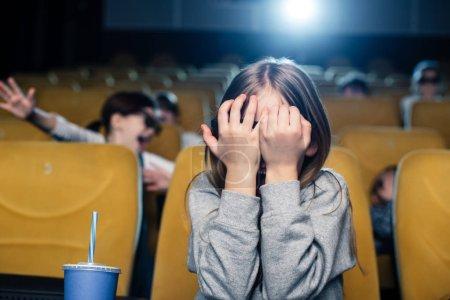 Photo pour Enfant effrayé, main dans la main sur le visage tout en regardant le film au cinéma - image libre de droit