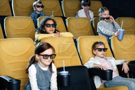 Foto de Sonrientes amigos multiculturales en gafas 3d viendo la película en el cine - Imagen libre de derechos