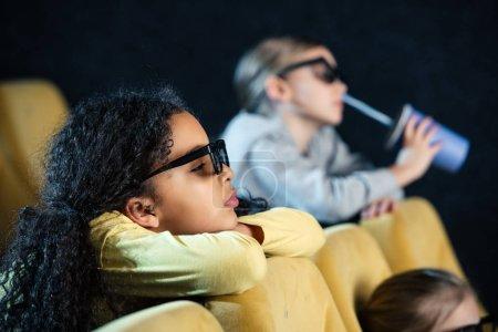 Photo pour Mise au point sélective des amis multiculturels, regarder le film au cinéma ensemble - image libre de droit