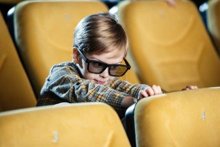 Photo pour Mignon garçon souriant à lunettes 3d assis dans le siège de cinéma confortable - image libre de droit