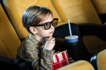 Photo pour Adorable garçon à lunettes 3d tenant la tasse de papier avec pop-corn - image libre de droit