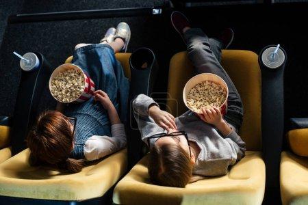 Photo pour Vue aérienne des amis manger des pop corn et regarder le film au cinéma - image libre de droit