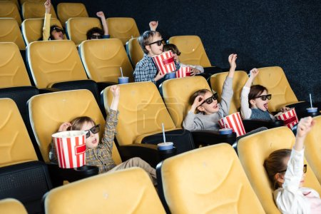 Photo for Excited multicultural friends showing win gesture while watching movie together - Royalty Free Image