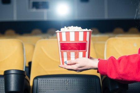 Photo pour Vue partielle de l'enfant tenant dépouillé de gobelet en papier à pop-corn au cinéma - image libre de droit