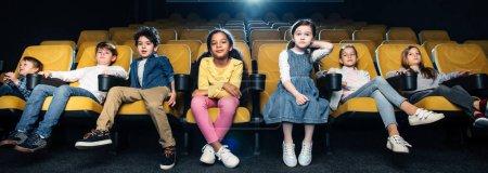 Photo pour Prise de vue panoramique d'amis multiculturels passant du temps au cinéma ensemble - image libre de droit