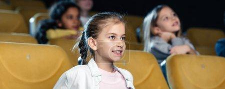 Photo pour Prise de vue panoramique de mignon enfant regardant le film au cinéma avec des amis multiculturelles - image libre de droit