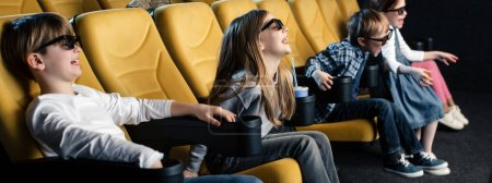 panoramic shot of exited friends in 3d glasses watching movie together