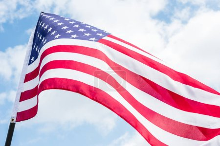 Photo pour Vue de bas angle du drapeau américain avec des étoiles et des rayures contre le ciel bleu - image libre de droit
