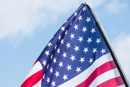 Photo pour Drapeau américain avec des étoiles et des rayures contre le ciel avec des nuages - image libre de droit