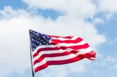 low angle view of flag with stars and stripes against blue sky