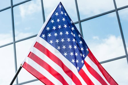 low angle view of american flag near glass building with windows