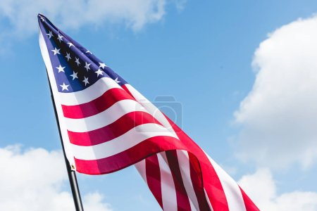 Photo for Low angle view of stars and stripes on american flag against blue sky with clouds - Royalty Free Image