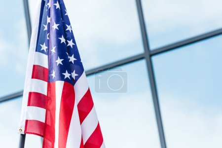 stars and stripes on american flag near building with sky reflection on windows