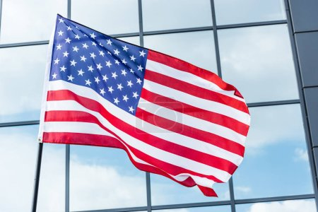 Photo for Stars and stripes on flag of america near building with glass windows and sky reflection - Royalty Free Image
