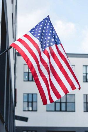 Photo pour Étoiles et rayures sur le drapeau de l'Amérique près de la construction - image libre de droit