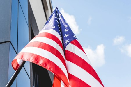 vista de ángulo bajo de la bandera nacional de América con estrellas y rayas cerca de la construcción