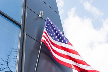 Niedrigwinkel-Ansicht der amerikanischen Nationalflagge mit Sternen und Streifen in der Nähe von Gebäuden gegen blauen Himmel mit Wolken