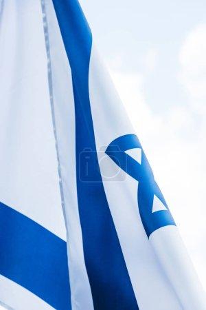 Photo pour Fermez-vous vers le haut du drapeau national d'Israël contre le ciel avec des nuages - image libre de droit