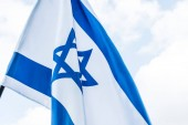 national flag of israel with star of david against sky with clouds